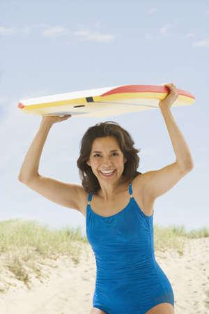 boogie: Hispanic woman holding boogie board over head
