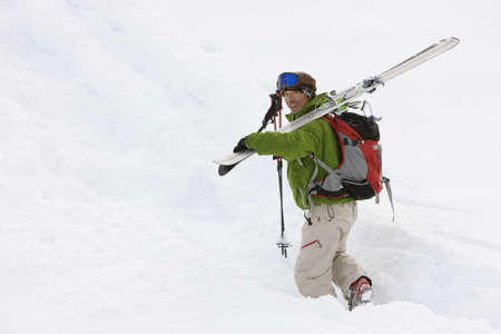 jeopardizing: Asian man carrying skis in snow LANG_EVOIMAGES