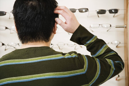 seriousness skill: Asian man shopping for eyeglasses LANG_EVOIMAGES