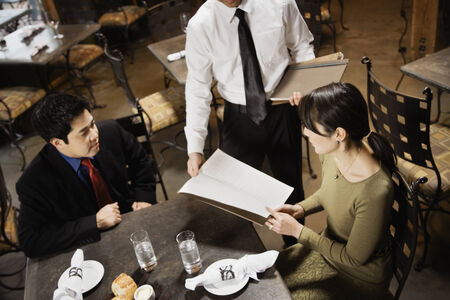 vietnamese ethnicity: Asian couple reading menu at restaurant LANG_EVOIMAGES