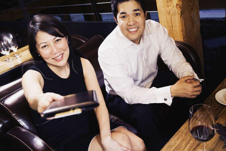 Asian couple paying restaurant bill Imagens