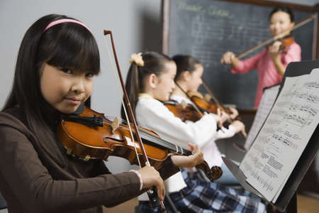 bowing head: Asian girl playing violin in music class