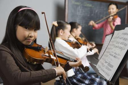 violines: Muchacha asi�tica que juega el viol�n en la clase de m�sica
