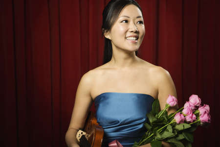 prevailing: Asian woman holding violin and flowers on stage LANG_EVOIMAGES