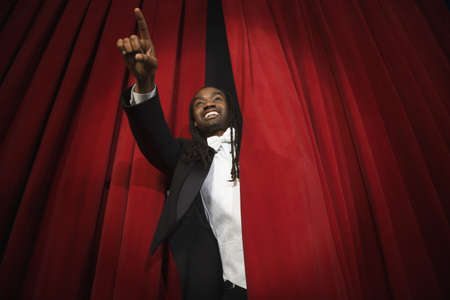 African man pointing through stage curtain Stock Photo