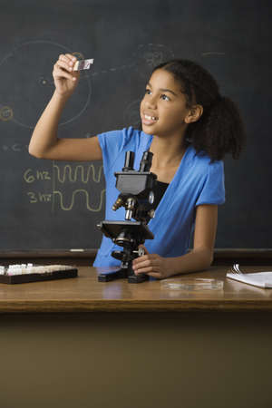 microscope slide: Mixed Race girl looking at microscope slide LANG_EVOIMAGES