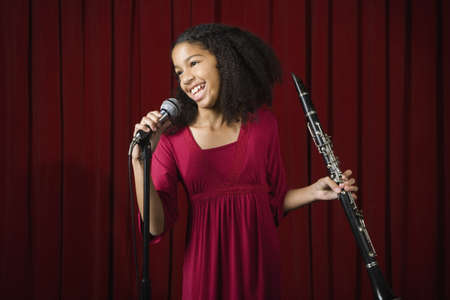 thanking: Mixed Race girl holding clarinet on stage
