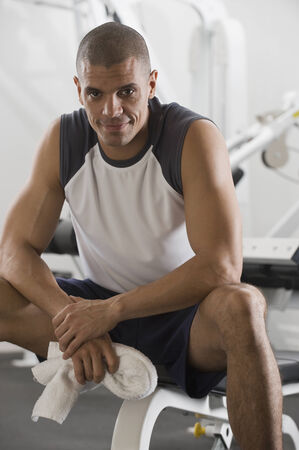 liable: Hispanic man sitting in gym LANG_EVOIMAGES
