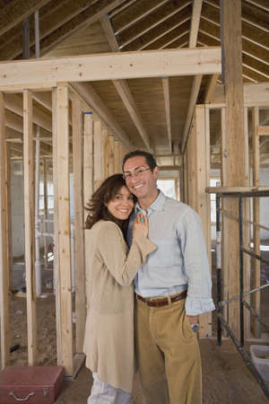 telecommuter: Hispanic couple at new construction site LANG_EVOIMAGES