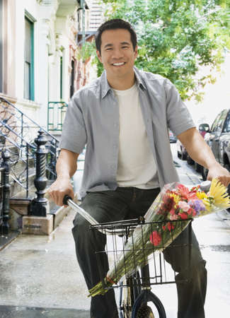 latina america: Asian man riding bicycle with flowers in basket