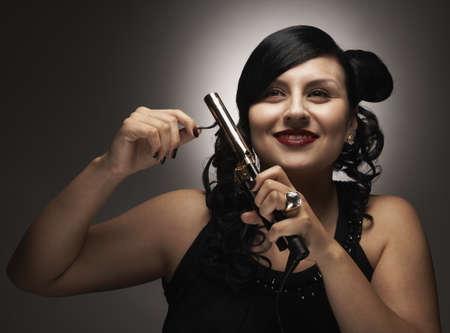 spiraling: Hispanic woman curling hair with curling iron LANG_EVOIMAGES