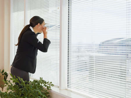 paranoia: Mixed race businesswoman peering out window