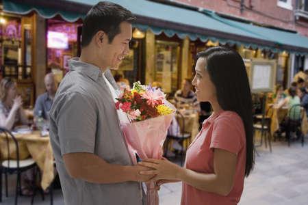 honeymooner: Asian man giving flowers to girlfriend