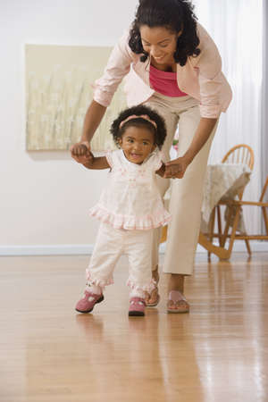 20 23 years: African mother helping daughter walk