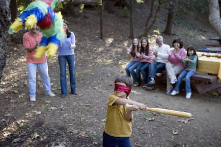 pinata: Hispanic boy swinging at pinata LANG_EVOIMAGES