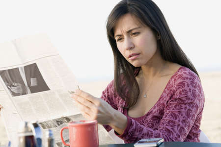 outmoded: Hispanic woman reading newspaper
