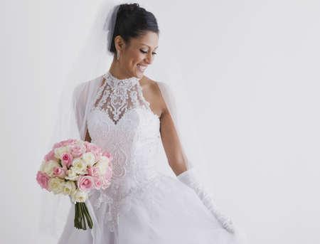 milepost: Hispanic bride holding bouquet LANG_EVOIMAGES