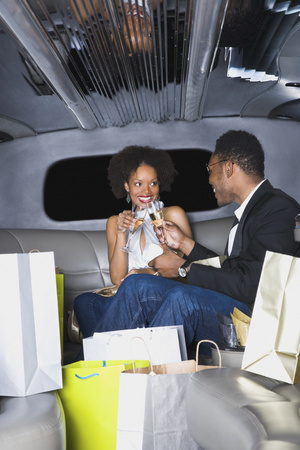 African couple toasting with champagne in limousine Zdjęcie Seryjne