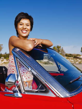 adventuresome: Mixed race woman in red convertible LANG_EVOIMAGES