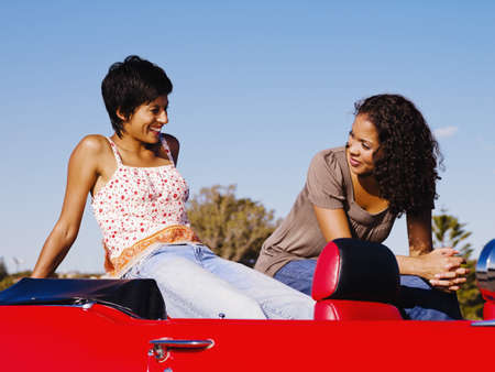 Two women sitting on back of red convertible Stock Photo