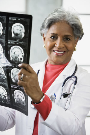 seriousness skill: African female doctor looking at x-rays