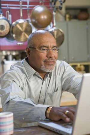 gramma: African man working on laptop in kitchen LANG_EVOIMAGES