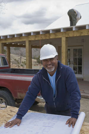 mid life: African foreman working with blueprints at construction site