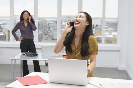 office furniture: Korean businesswoman talking on cell phone in office