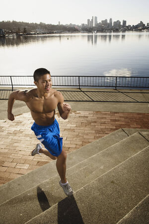 Bare chested Asian man jogging along urban waterfront