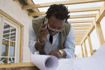 prevailing: African man on cell phone looking at blueprints
