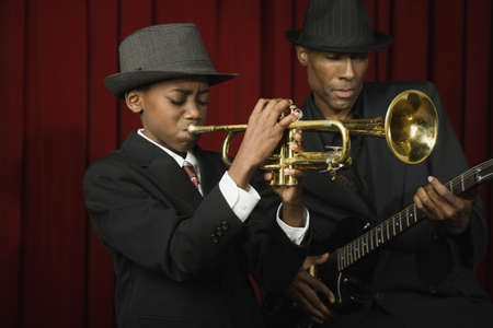 unknown age: African man and boy in suits playing guitar and trumpet