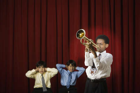 seriousness skill: African boy playing trumpet with multi-ethnic classmates covering ears