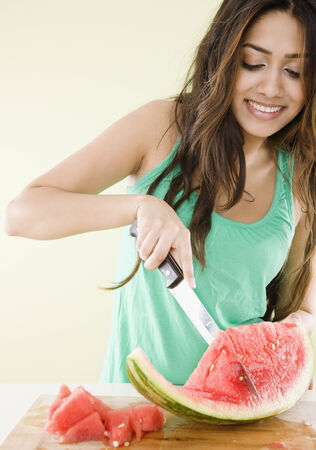 Middle Eastern woman cutting watermelon LANG_EVOIMAGES