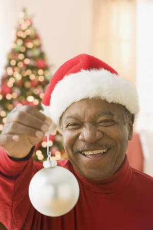 milepost: African man wearing Santa hat and holding Christmas ornament LANG_EVOIMAGES