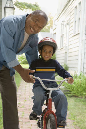 gusto: African grandfather teaching grandson to ride bicycle LANG_EVOIMAGES