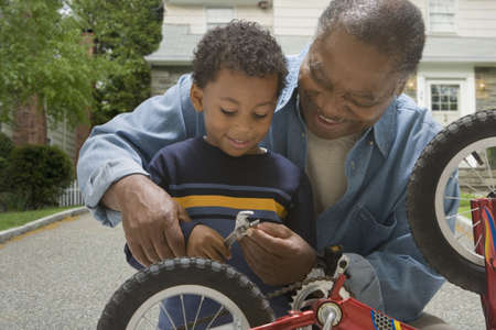 security gap: African grandfather and grandson fixing bicycle