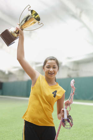 front raise: Mixed race girl lacrosse player holding trophy