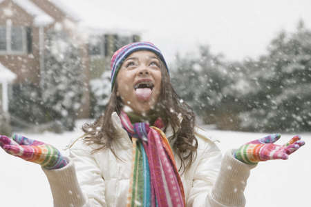 Mixed race girl with mouth open in snow