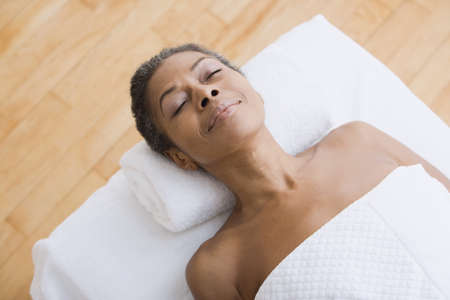 women only: Mixed race woman laying on massage table with eyes closed