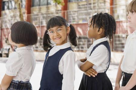 nios en la escuela: Ni�os de las escuelas multi�tnicas en los uniformes en fila al aire libre LANG_EVOIMAGES