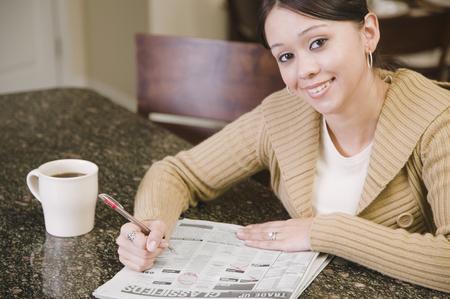 woman searching: Hispanic woman searching newspaper classified ads