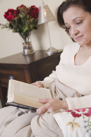 daydreamer: Mixed race woman reading in bed