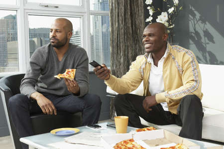 shrieking: African men watching television and eating pizza in living room