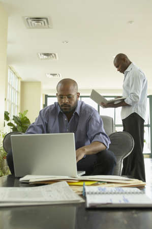 telecommuter: African businessmen working on laptops in office LANG_EVOIMAGES