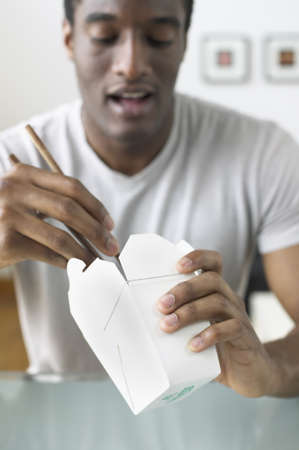 take out: African man eating out of Chinese take out box LANG_EVOIMAGES