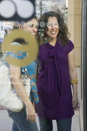german ethnicity: Multi-ethnic women standing in shop window LANG_EVOIMAGES