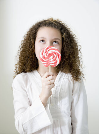 obscured face: Mixed race girl with oversized lollipop