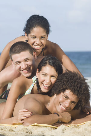 Multi-ethnic friends laying in pile on beach Banco de Imagens