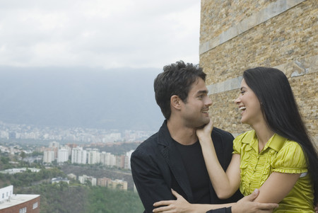 Hispanic couple laughing in urban setting