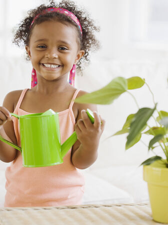 relishing: Mixed race girl watering plants LANG_EVOIMAGES